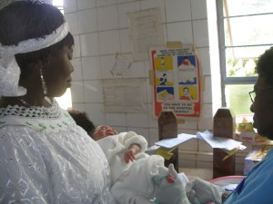 A mother holds her newborn while a blood sample for sickle cell testing is taken